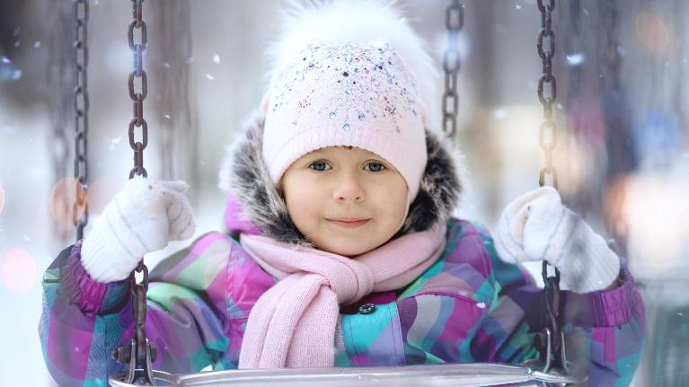 little girl wearing a coat on a swing | kids dentist palos heights il