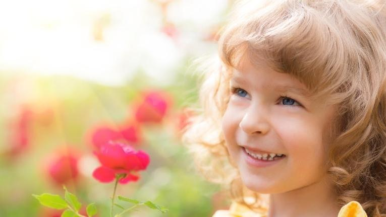 smiling little girl with flowers | Pediatric Restorative Dentistry in Palos Heights